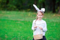 拿着一个篮子用复活节彩蛋的可爱的小女孩佩带的兔宝宝耳朵在春日 免版税库存照片