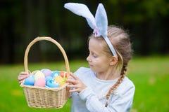 拿着一个篮子用复活节彩蛋的可爱的小女孩佩带的兔宝宝耳朵在春日 库存照片