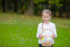 拿着一个篮子用复活节彩蛋的可爱的小女孩在春日户外 图库摄影