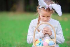 拿着一个篮子用复活节彩蛋的逗人喜爱的小女孩佩带的兔宝宝耳朵在春日 免版税库存图片