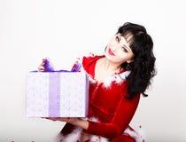 拿着一个精密圣诞节礼物箱子的红色外套的年轻和美丽的妇女 库存照片