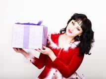 拿着一个精密圣诞节礼物箱子的红色外套的年轻和美丽的妇女 库存图片
