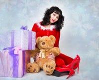 拿着一个精密圣诞节礼物箱子的红色外套的年轻和美丽的妇女 免版税库存图片