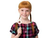 拿着一个糖果用樱桃的小红发女孩 库存照片