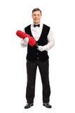 拿着一个红色喷粉器的快乐的男管家 免版税库存照片