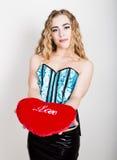 拿着一个红色心脏枕头的蓝色束腰的年轻和美丽的卷曲女孩 库存图片