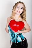 拿着一个红色心脏枕头的蓝色束腰的年轻和美丽的卷曲女孩 图库摄影