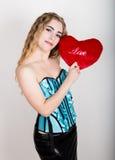 拿着一个红色心脏枕头的蓝色束腰的年轻和美丽的卷曲女孩 免版税库存照片