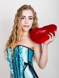 拿着一个红色心脏枕头的蓝色束腰的年轻和美丽的卷曲女孩 免版税库存图片