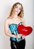拿着一个红色心脏枕头的蓝色束腰的年轻和美丽的卷曲女孩 库存照片