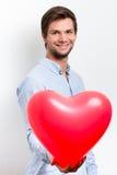 拿着一个红色心脏气球的人 库存照片
