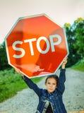 拿着一个红色标志的小女孩 免版税库存照片
