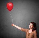 拿着一个红色气球的妇女 免版税图库摄影