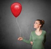 拿着一个红色气球的妇女 库存图片