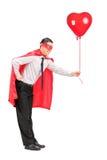拿着一个红色气球的超级英雄服装的人 免版税库存图片