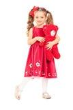拿着一个红色玩具熊的逗人喜爱的小女孩 免版税图库摄影