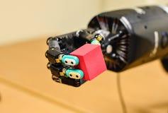 拿着一个红色立方体的机械机器人手在研究实验室 免版税库存图片