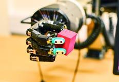 拿着一个红色立方体的机械机器人手在研究实验室 免版税图库摄影
