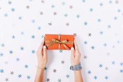 拿着一个红色箱子的美好的女性手 免版税库存照片