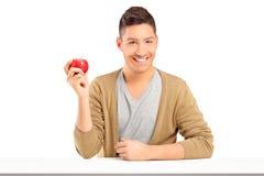 拿着一个红色苹果和摆在表的英俊的微笑的人 免版税库存图片