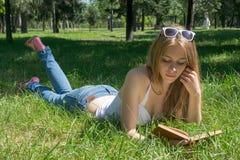 拿着一个红色苹果和读一本书的女孩在夏天公园 免版税库存照片