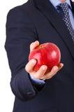 拿着一个红色苹果的商人。 图库摄影