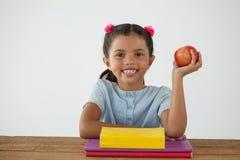 拿着一个红色苹果的女小学生反对白色背景 免版税库存照片