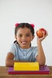 拿着一个红色苹果的女小学生反对白色背景 免版税库存图片