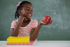 拿着一个红色苹果的女小学生反对白色背景 库存图片