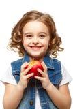 拿着一个红色苹果的牛仔布夹克的小女孩。 库存照片