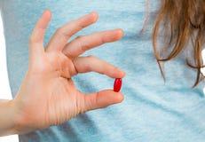 拿着一个红色药片的手指。 免版税库存图片