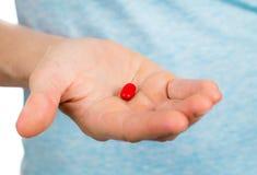 拿着一个红色药片的手特写镜头。 免版税库存图片