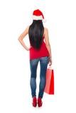 拿着一个红色袋子的圣诞节帽子的一名妇女 免版税库存照片