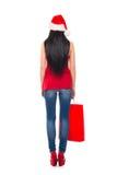 拿着一个红色袋子的圣诞节帽子的一名妇女 免版税库存图片