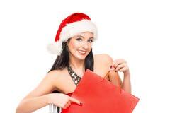 拿着一个红色袋子的圣诞节帽子的一名愉快的妇女 免版税图库摄影