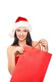 拿着一个红色袋子的圣诞节帽子的一名愉快的妇女 免版税库存照片