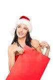 拿着一个红色袋子的圣诞节帽子的一名愉快的妇女 免版税库存图片
