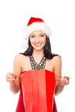 拿着一个红色袋子的圣诞节帽子的一名愉快的妇女 库存照片