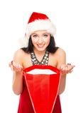 拿着一个红色袋子的圣诞节帽子的一名愉快的妇女 图库摄影