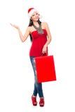 拿着一个红色袋子的圣诞节帽子的一名愉快的妇女 库存图片