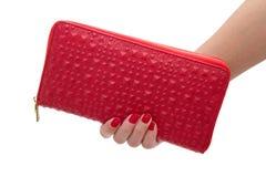 拿着一个红色钱包的被隔绝的女性手 免版税库存图片