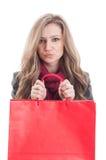 拿着一个红色购物袋的逗人喜爱和可爱的女性 免版税库存图片