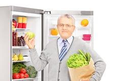 拿着一个纸袋的微笑的成熟人在冰箱旁边 库存照片