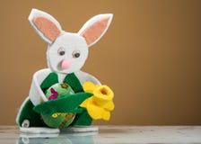 拿着一个绿色复活节彩蛋的一只白色复活节兔子的小雕象 免版税库存照片
