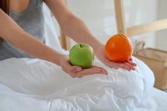 拿着一个绿色苹果和桔子在手上的年轻健康妇女 免版税库存照片