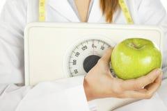 拿着一个绿色苹果和重量缩放比例的营养学家 图库摄影