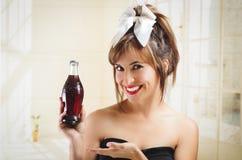 拿着一个老葡萄酒古柯的美丽的减速火箭的女孩 免版税库存照片
