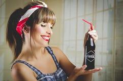 拿着一个老葡萄酒古柯的美丽的减速火箭的女孩 库存图片