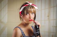 拿着一个老葡萄酒古柯的美丽的减速火箭的女孩 免版税库存图片