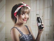 拿着一个老葡萄酒古柯的美丽的减速火箭的女孩 免版税图库摄影